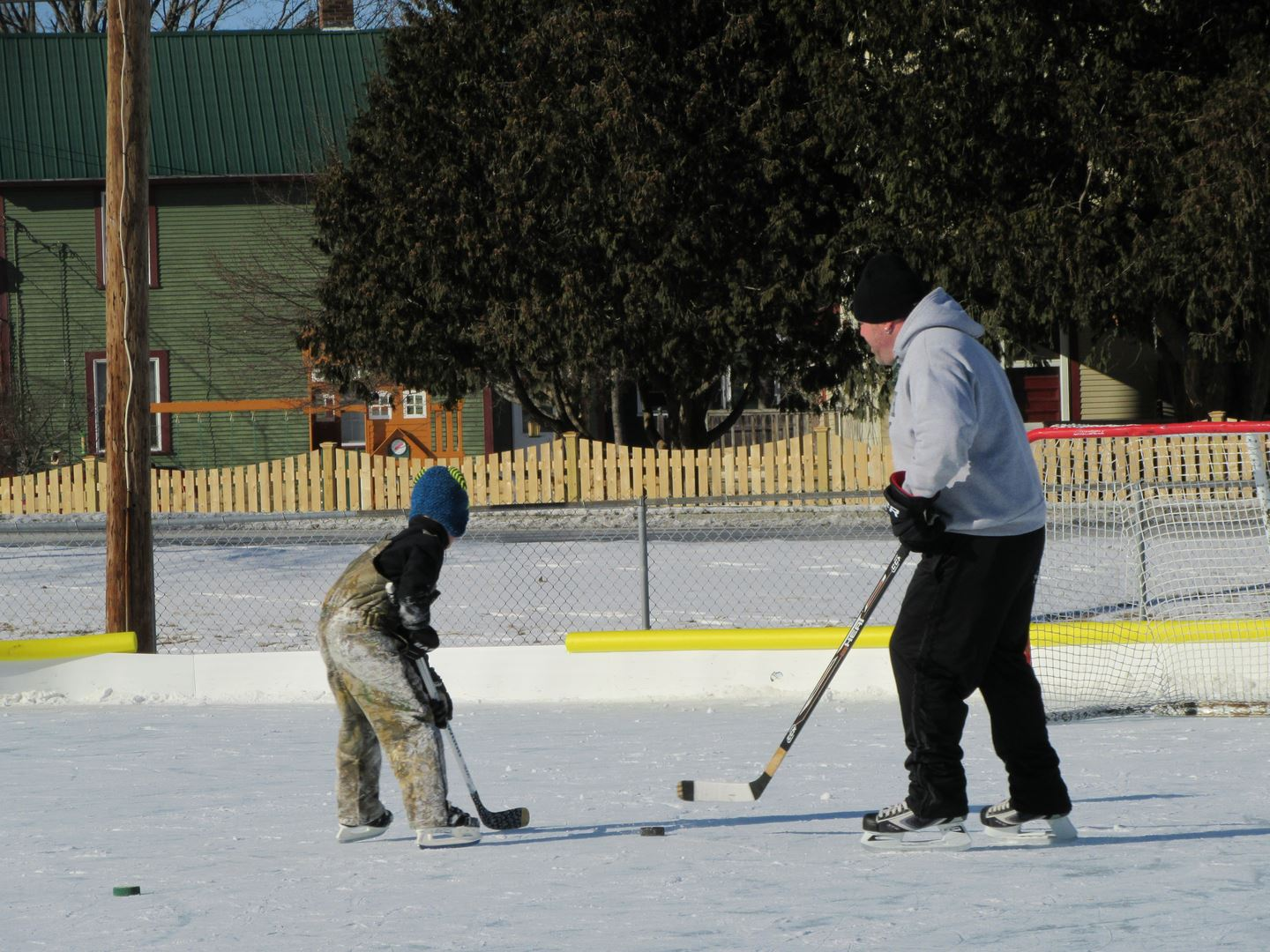Man and boy playing hockey on Pat Walsh Ice Rink